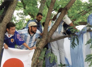Argentine and Japanese fans share a tree to get a view of the game
