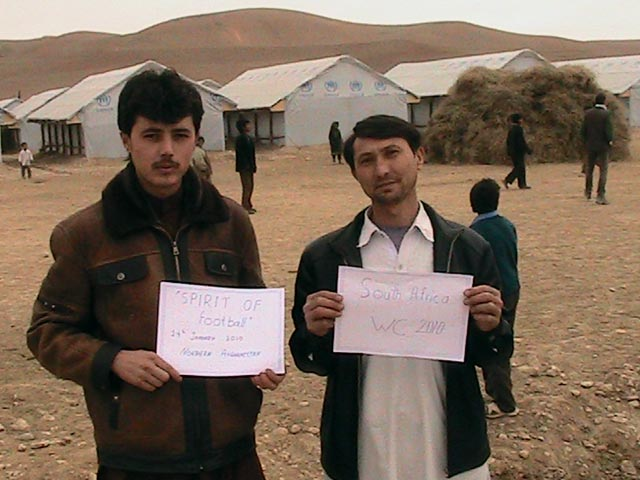 Two Afghan men hold messages of support for The Ball