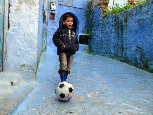 A child kicks The Ball in a Chefchaouen street