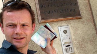 Phil proudly shows off our Ivory Coast visas