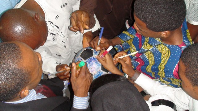 Churchgoers eagerly sign The Ball after the service