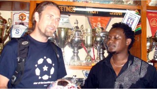 John Ndichu Ng'ethe and Andrew in front of MYSA's trophy cabinet