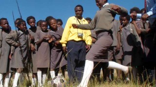 School girls line up to kick The Ball in Lusaka