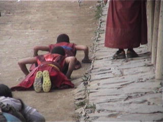 Young monks prostrate themselves in football boots