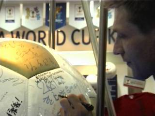 Chris signs the ball in the official souvenir shop in Seoul